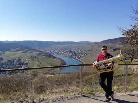 Oliver mit der Tuba vor dem sonnigen Kröver Moseltal